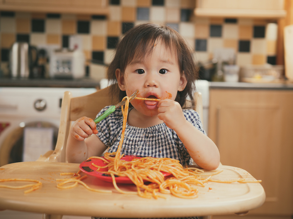 child eating spaghetti in high chair
