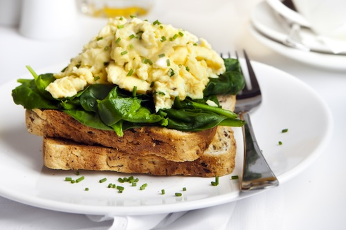 Scrambled eggs on toast, with wilted spinach.