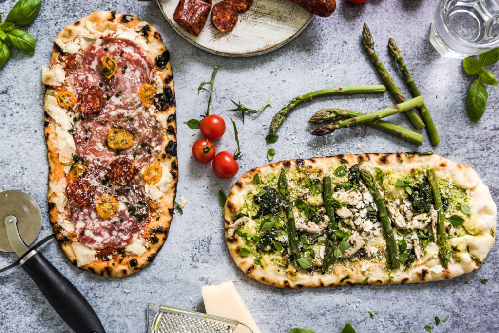 Pizza for sharing, from above on slate background, flat lay ingredients