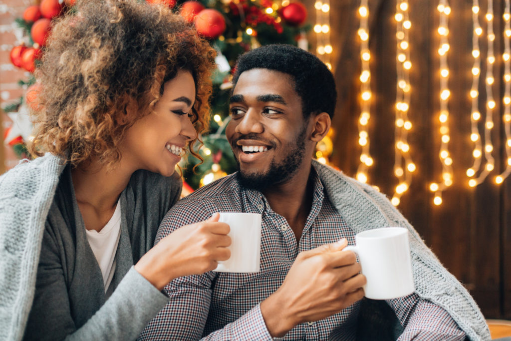 Happy young black couple drinking coffee and enjoying Christmas morning together