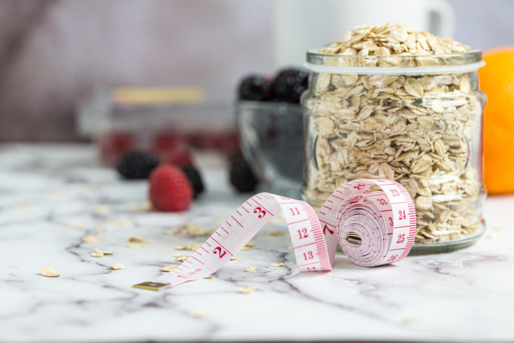 Measuring tape, oats and fresh berries for healthy slimming diet concept
