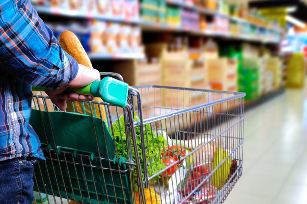 Man pushing shopping cart full of food in the supermarket aisle